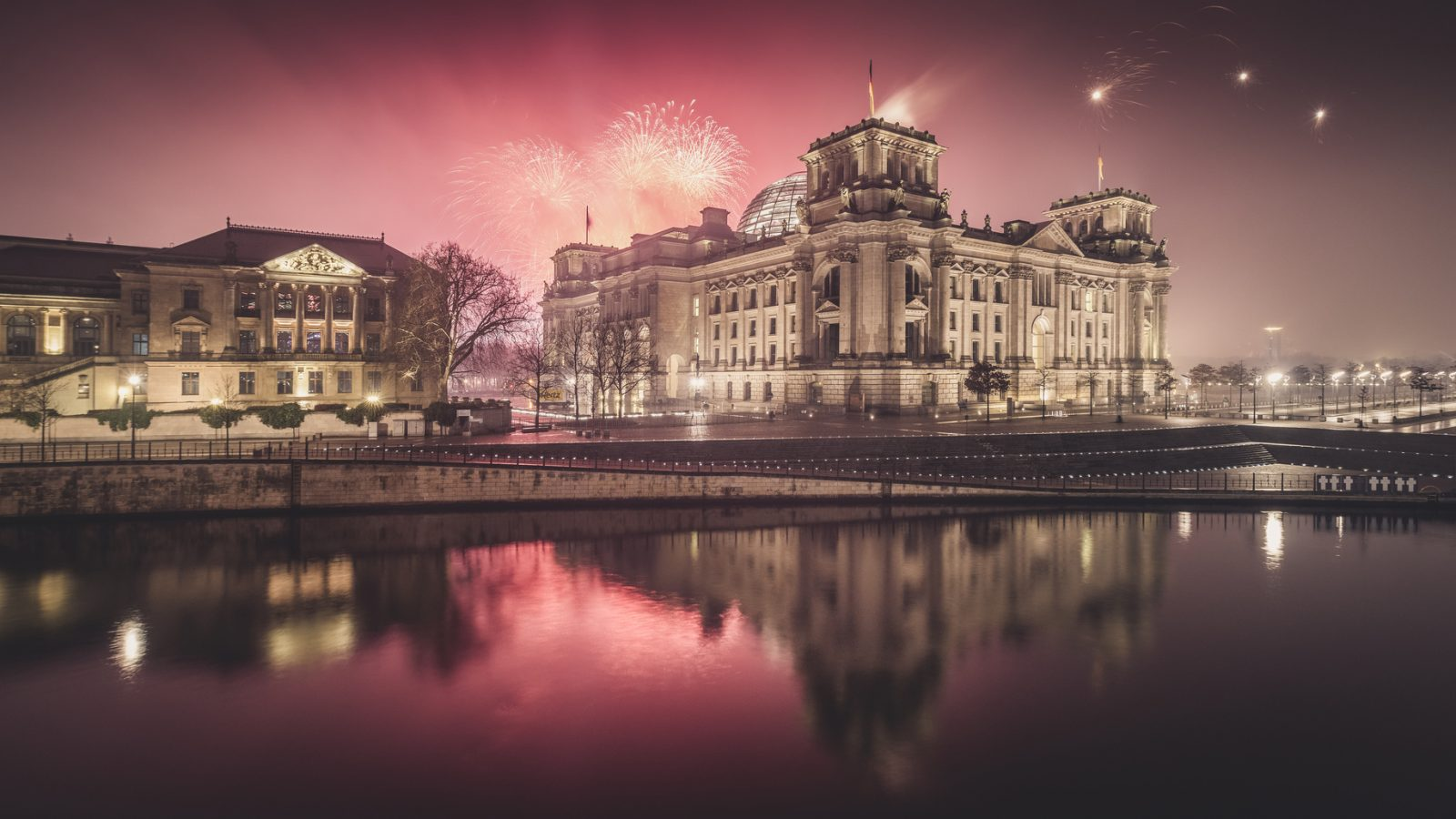 Berlin's Reichstag building by night, shot from the other side of the Spree, with fireworks in the background. Picture used to illustrate an article on plans for a moat for the Reichstag.