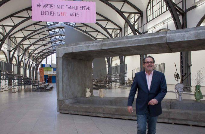 Udo Kittelmann  in der historischen Halle des Hamburger Bahnhofs. Von der Decke hängt eine Arbeit von Mladen Stilinovi, hinter ihm eine Arbeit von  Goshka MacugaFoto: Patricia Schichl