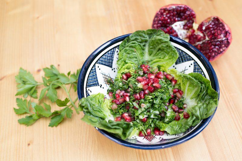 Salat mit Granatapfelkernen auf Holztisch mit Petersilienzwei und Granatapfel im Hintergrund. Das Restaurant in Friedrichshain ist noch offen.
