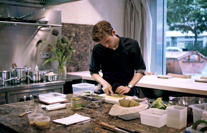 Dylan Watson-Brawn an der Kochinsel in seinem Restaurant Ernst. Das Restaurant verkauft zurzeit Gemüse- und Kochkisten.