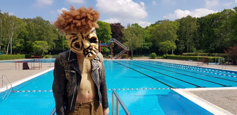 """Mann mit Lederjacke und Maske aus dem Theaterstück """"The White Walkers Sans Amour"""" vor dem Schwimmbecken des Sommerbad Humboldthain."""
