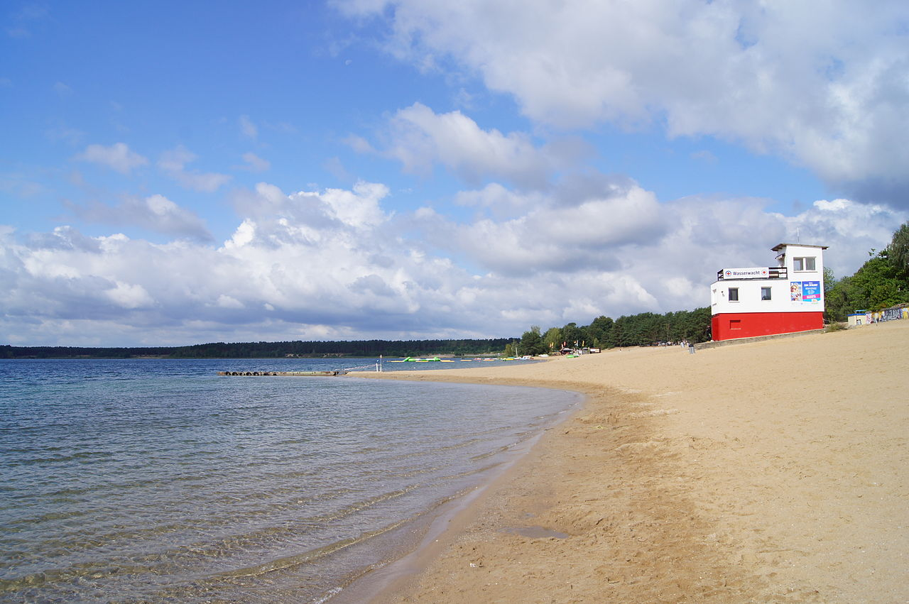 The sand beach by the lake Helenesee, with a red and white lifeguard building or hut in the corner of the picture.