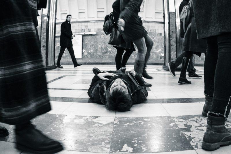 Schwarzweißfotografie, ein Mann liegt auf dem Boden, während andere an ihm vorbeilaufen. Teil des experimentellen Theaterstücks Implicit Impacts von Transformator.