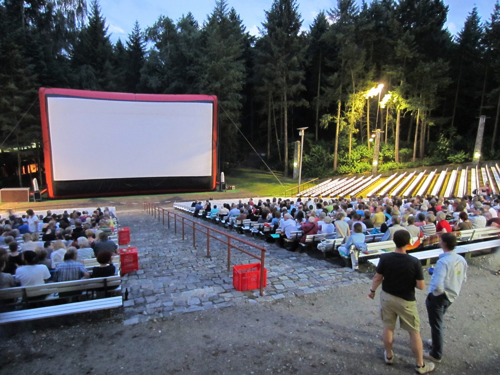 Open air cinema Rehberge by dusk, people sitting on benches, screen is white.