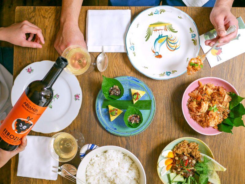 Tisch von oben fotografiert mit vielen bunten Speisen und Hand mit Weinflasche, die gerade eingießt. Das Restaurant in Friedrichshain ist noch offen.