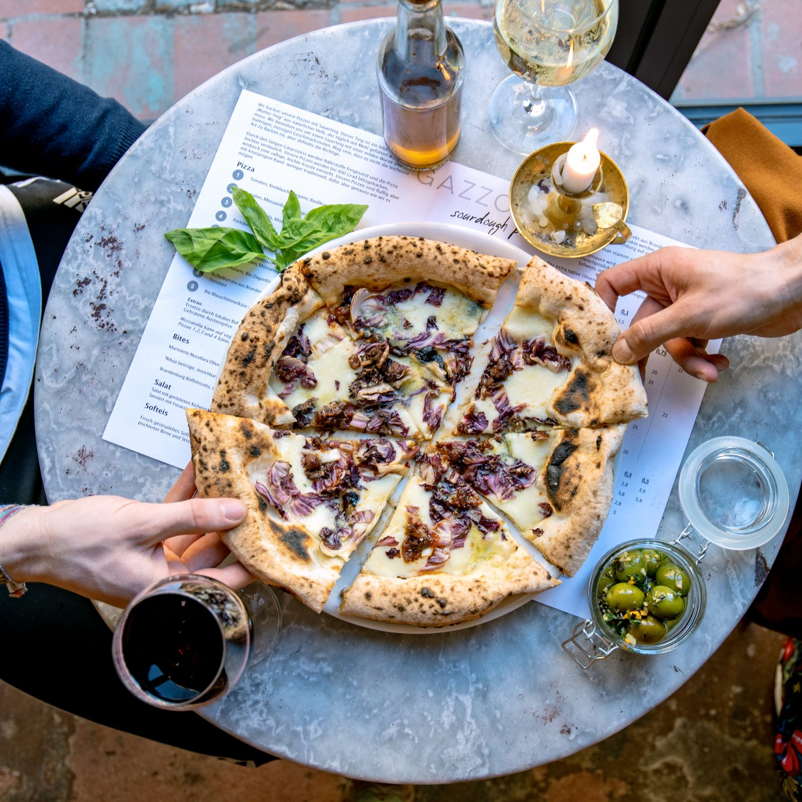 Sourdough pizza with a cheese and radicchio topping on a marble table with wine glasses, a candle and olives at Gazzo pizza.