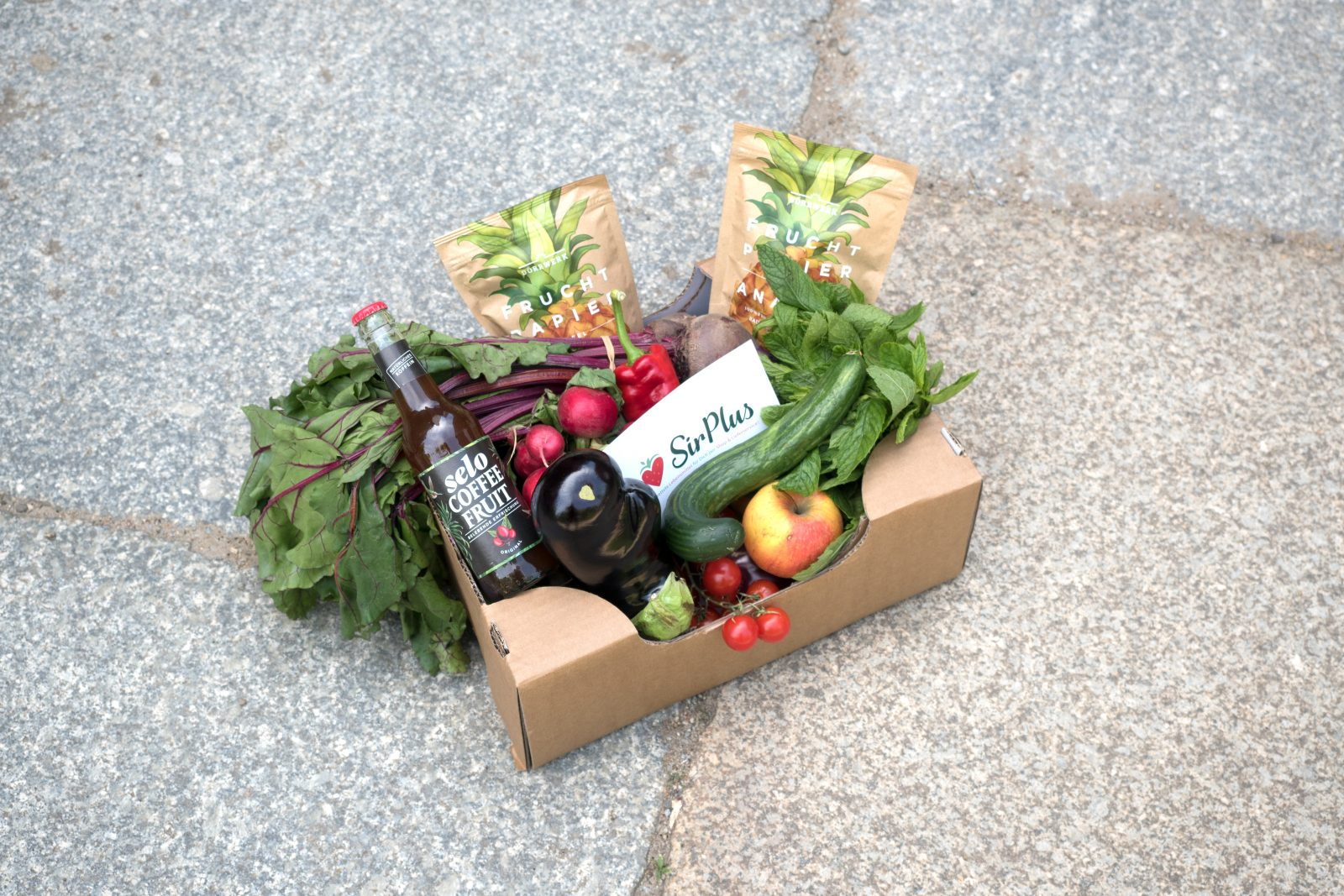 A box with fresh produce and other food products by Sir Plus on the pavement. Sir Plus is a Berlin-based start up combating food waste.