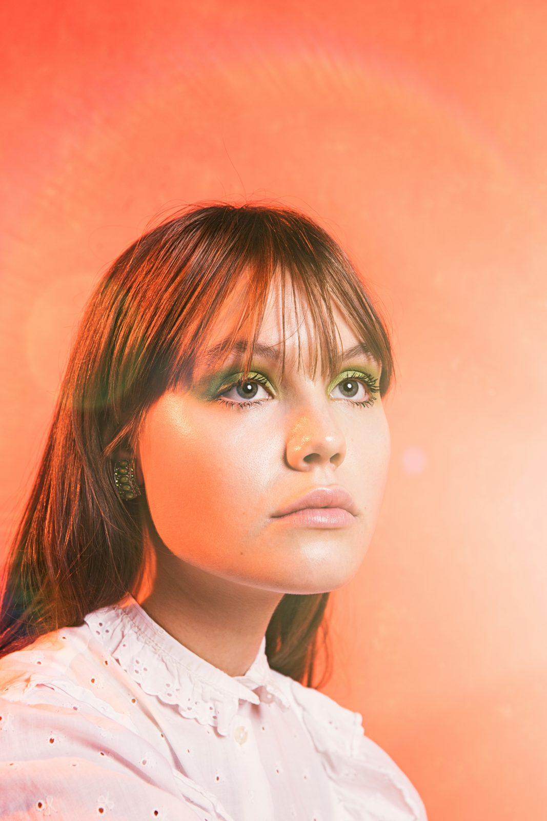 Woman with long her and white button shirt and green eye make up in front of light orange background. It is singer Lxandra.