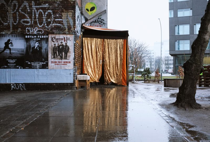 Door to club Golden Gate, hut with golden curtains next to brick wall, wet streets. Golden Gate is one of the clubs that has received funds through the noise insulation programme.