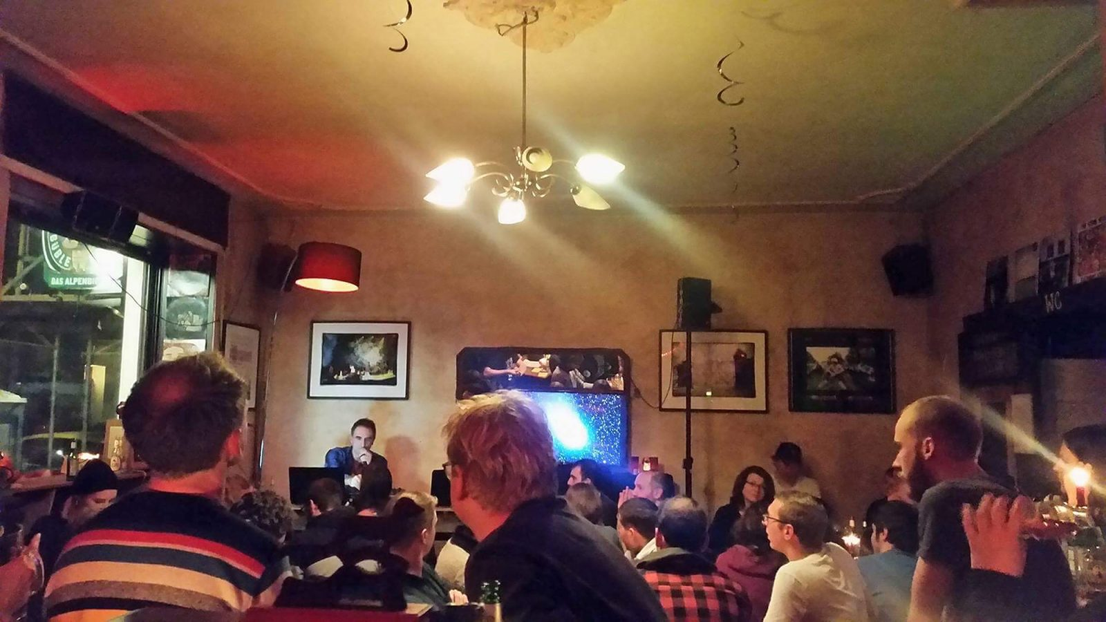 """View of interior of bar with visitors facing away from camera and a host facing the camera. Crowd at music quiz """"Welcome to the Working Week"""" at Posh Teckel Neukölln."""