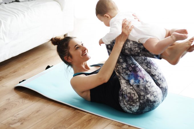 Mother and baby exercising on yoga mat at home model released Symbolfoto property released PUBLICATIONxINxGERxSUIxAUTxHUNxONLY ABIF00336