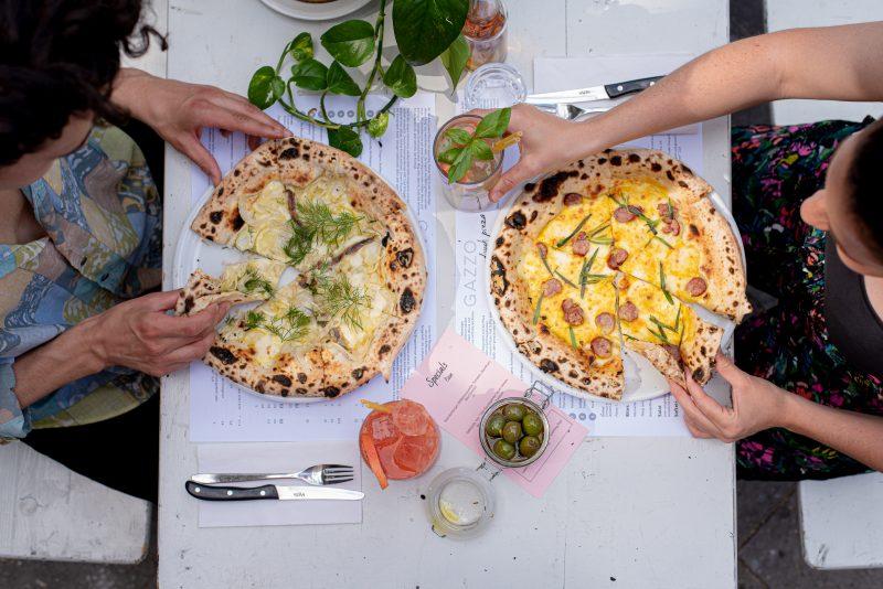Blick von oben auf zwei Frauen an weißem Tisch mit Pizzen, Oliven und Drinks. das Restaurant in Neukölln ist noch offen.