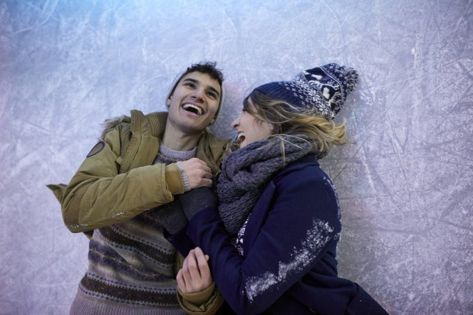 Laughing couple lying on an ice rink at night model released Symbolfoto property released PUBLICATIONxINxGERxSUIxAUTxHUNxONLY ZEDF01896 | imago images / Westend61