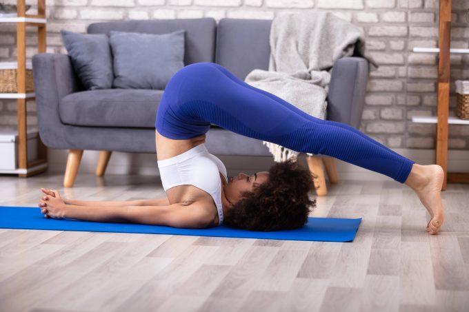 Woman Practicing Plow Pose On Yoga Mat ,model released, Symbolfoto PUBLICATIONxINxGERxSUIxAUTxONLY Copyright: xAndreyPopovx Panthermedia26325857
