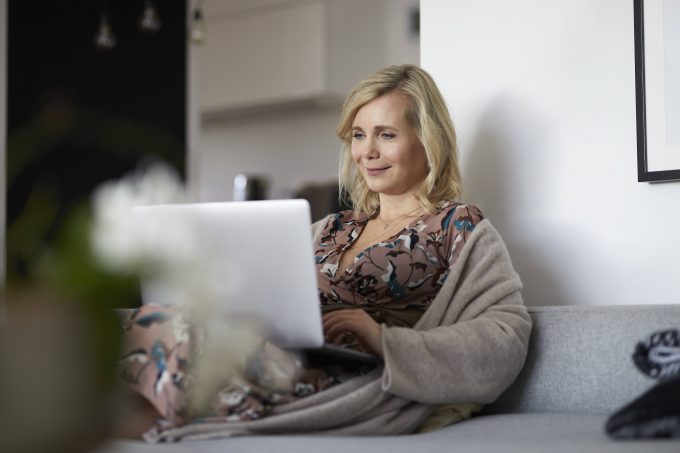 Blond woman using laptop on couch at home model released Symbolfoto property released PUBLICATIONxINxGERxSUIxAUTxHUNxONLY RBF07058