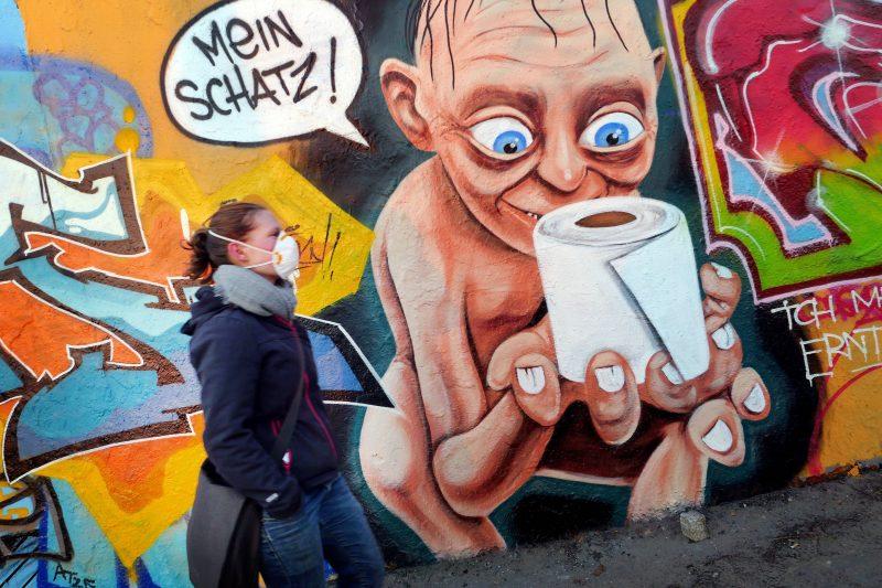Graffito im Mauerpark zeigt Gollum mit einer Rolle Toilettenpapier, Frau mit Atemschutzmaske läuft an der frischen Luft. Foto: imago images / Sabine Gudath