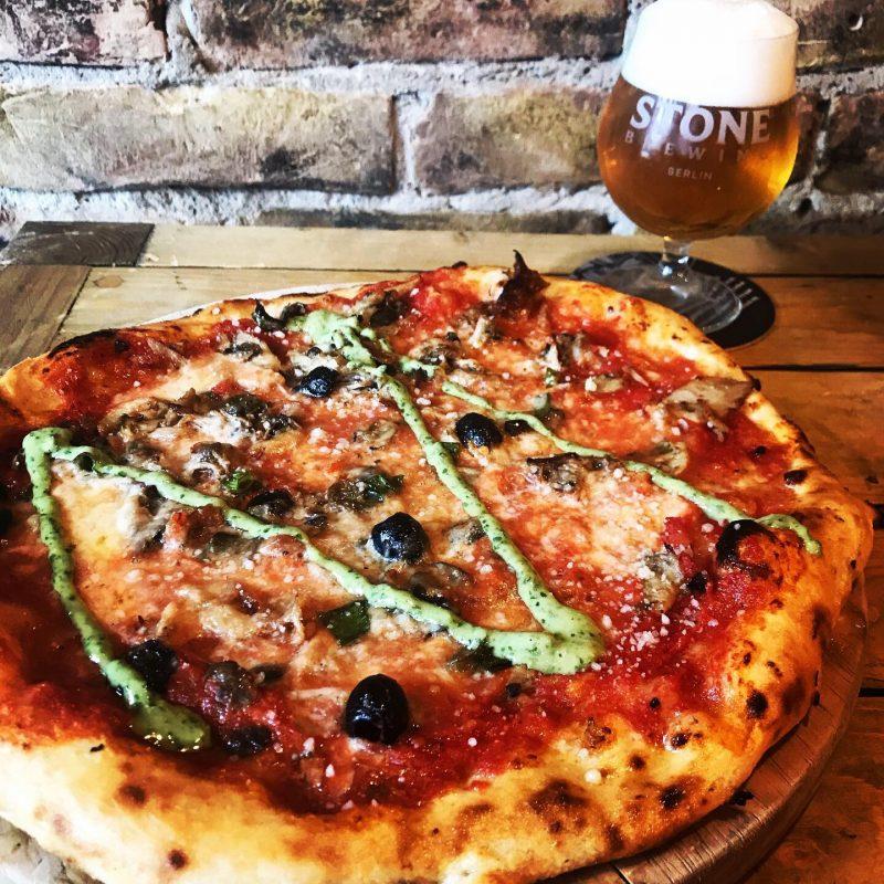 Pizza mit grüner Sauce, Bier im Hintergrund. Das Restaurant in Friedrichshain ist weiter offen