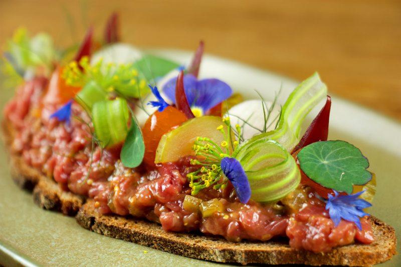 Tartar auf Brot mit essbares Blüten und Blättern belegt. Das Restaurant Christopher's in Charlottenburg ist noch offen