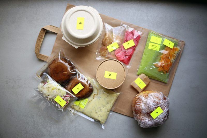 Verschiedene Lebensmittel zubereitet und verpackt auf Papiertüte, mit neongelben Labeln.