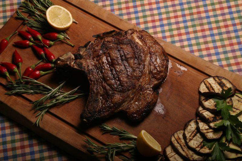 Steak auf Holzbrett und gegrillte Aubergine und Zucchini, garniert, Chili und Zitrone auf Tisch mit buntkarierter Tischdecke. Das Restaurant in Charlottenburg ist noch offen.