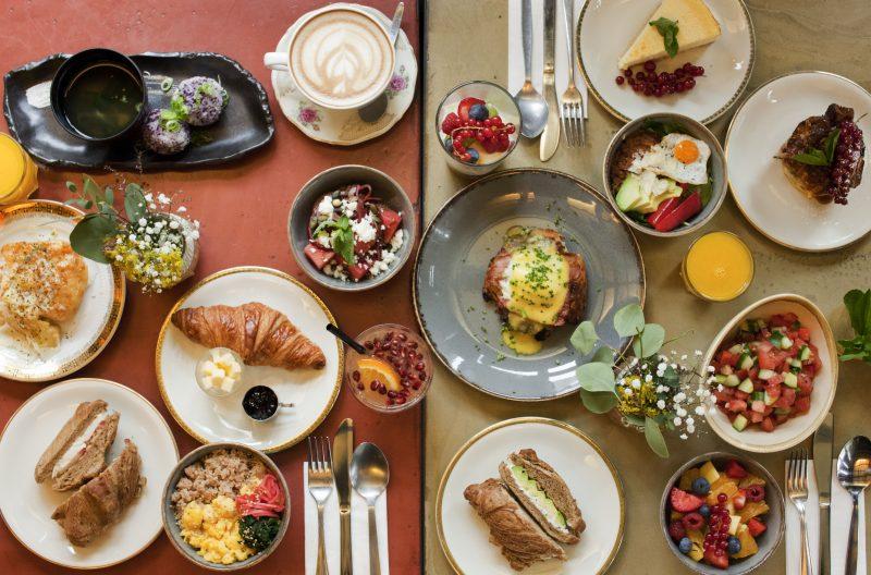 Vollgedeckter Tisch mit zahlreichen Speisen von oben fotografiert im House of Small Wonder. Das Restaraurant in Mitte ist noch offen.