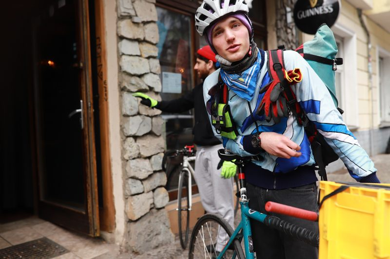 Fahrradfahrer vor Ladengeschäft. Ein Kurierfahrer des Lieferservice Kolyma 2