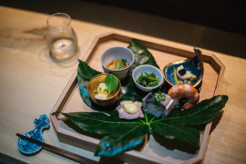 Kleine Schalen und Sushi auf Blatt auf Holztablett auf Holztheke, Essstäbchen und Wasserglas daneben. Das Restaurant Shiori in Mitte ist noch offen.