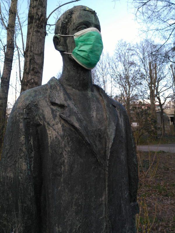 Eine Statue am Weißen See, die Mundschutz trägt.