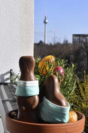 Osterhasen mit Mundschutz auf einem Balkon während der Coronakrise.