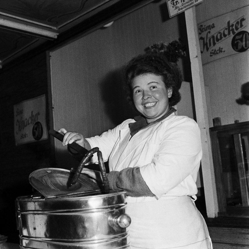 Imbissbudenverkäuferin und Knacker: Essen auf die Hand war schon immer eine Berliner Spezialität.