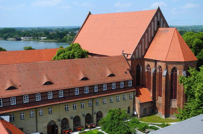 Der Blick vom Steintorturm auf das Dominikanerkloster Prenzlau, dahinter ist der Unteruckersee zu sehen. Foto: imago images/PEMAX