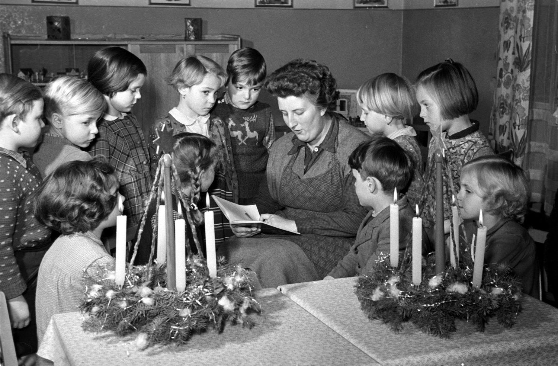Eine Kindheit in Berlin: Erzieherin liest Kindern aus einem Weihnachtsbuch vor, 1956.