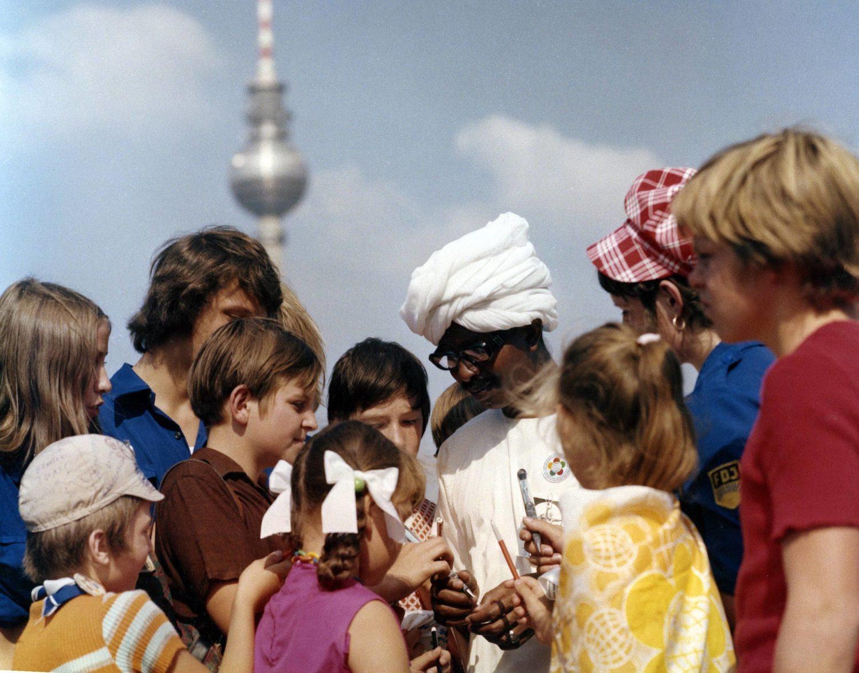 Eine Kindheit in Berlin: Jugendliche im Gespräch mit einem Mann mit Turban während der Weltfestspiele der Weltjugend in Berlin-Ost, Sommer 1973.