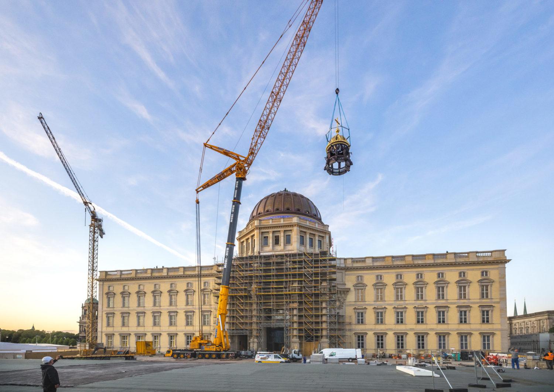 Südfront des rekonstruierten Berliner Schlosses. Auf dem Bild ist zu sehen, wie das historische Kreuz auf die Kuppel verfrachtet wird. Foto: David von Becker