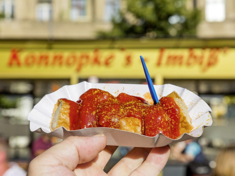 Die Currywurst zählt zu den Berliner Gerichten schlechthin. Konnopke's Imbiss im Hintergrund gilt als der erste Imbissstand im damaligen Ost-Berlin. Foto: Imago/Hettrich