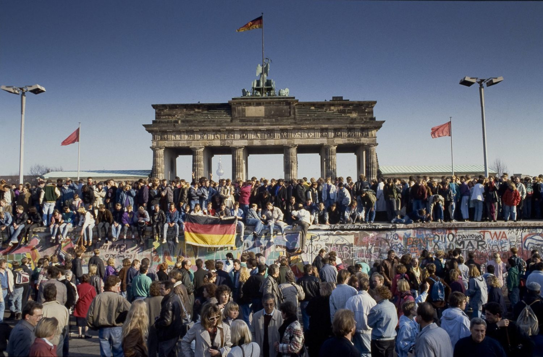 Menschen aus Ost und West feiern den Fall der Berliner Mauer am Brandenburger Tor, November 1989.