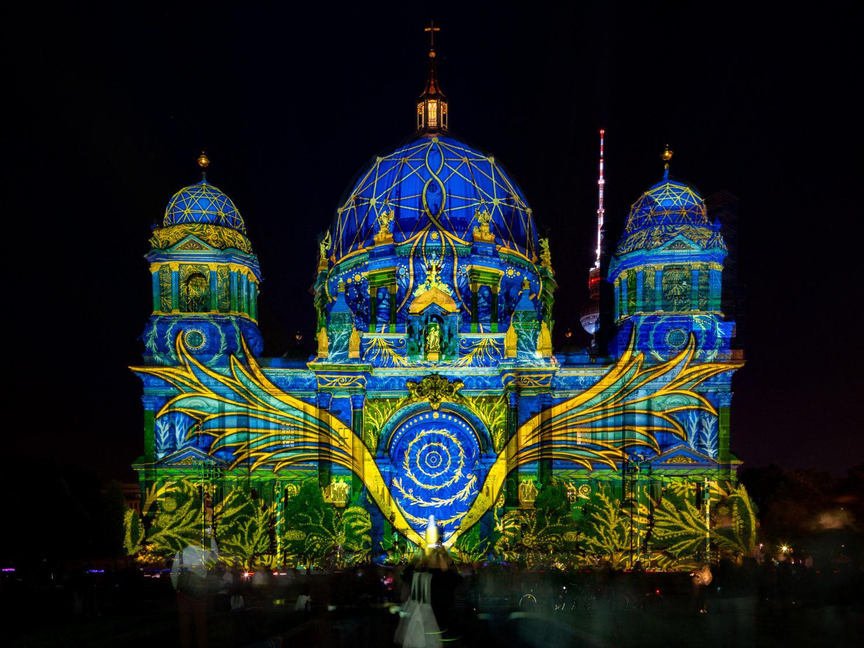 """Der Berliner Dom leuchtet beim """"Festival of Lights"""" 2020 in einem kräftigen Blau, über die Fassade spannt sich ein riesiger Flügel. Foto: Imago/JeanMW"""