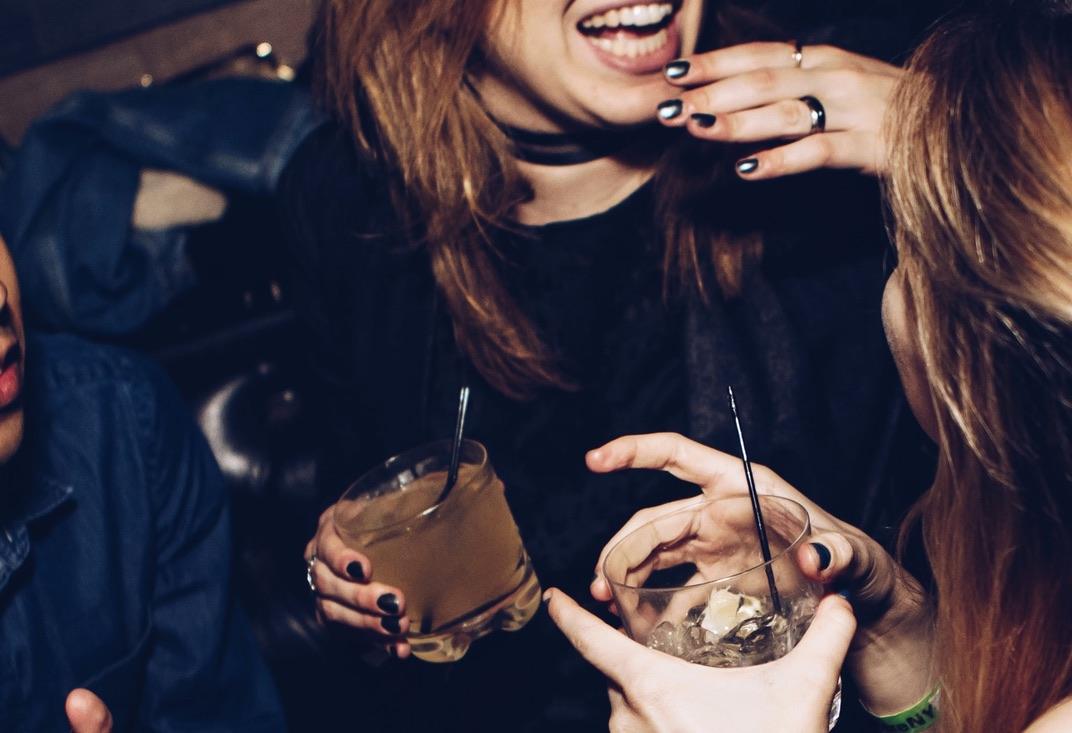 Zwei Frauen mit Cocktailgläsern in der Hand lachen und unterhalten sich.