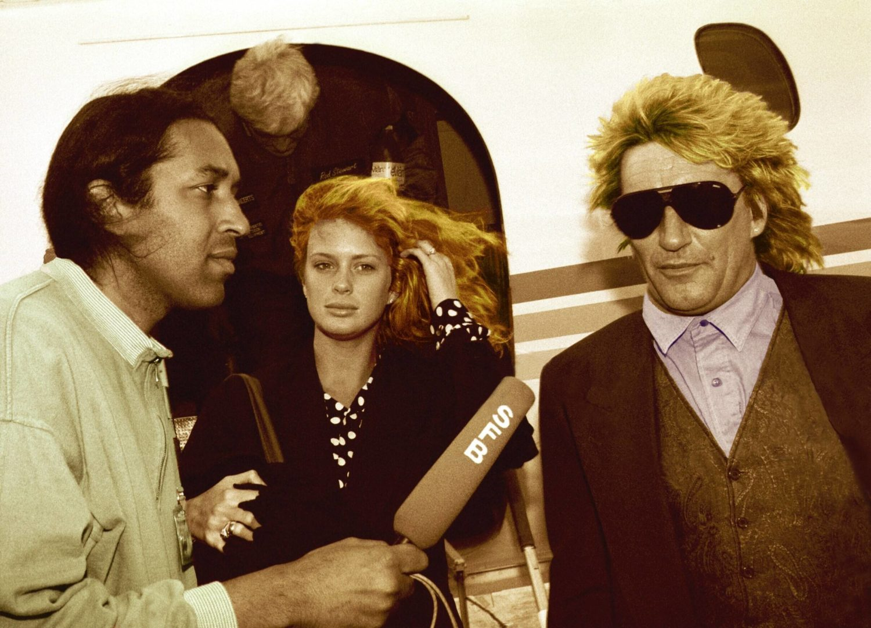 Rod Stewart und seine Frau Rachel Hunter landen im Frühling 1991 auf dem Flughafen Tegel. SFB Moderator Cherno Jobatey interviewt das prominente Paar. Foto: Imago/Brigani Art/Heinrich