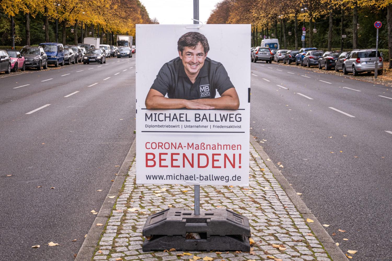 """Michaell Ballweg auf einem Plakat auf der Straße des 17. Juni. Der """"Querdenken""""-Gründer will seinen goldenen Aluhut unbedingt haben. Foto: Imago Images/Stefan Zeitz"""