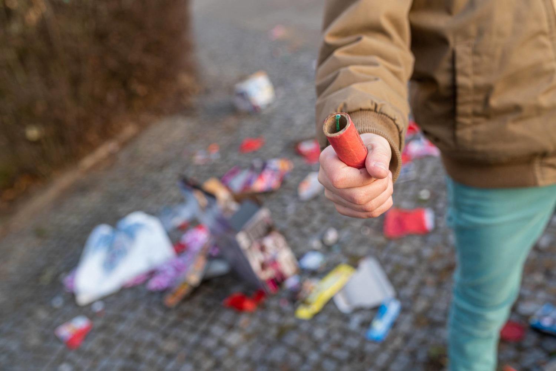 Mann mit einem Böllern in der Hand. Im Hintergrund liegt Müll von Feuerwerk auf der Straße.