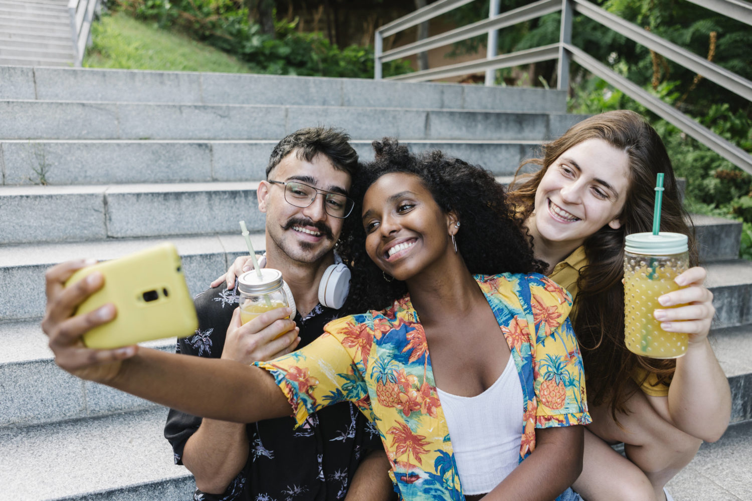 imago images / Westend61 Friends taking selfie on smart phone while sitting in public park model released Symbolfoto XLGF00570