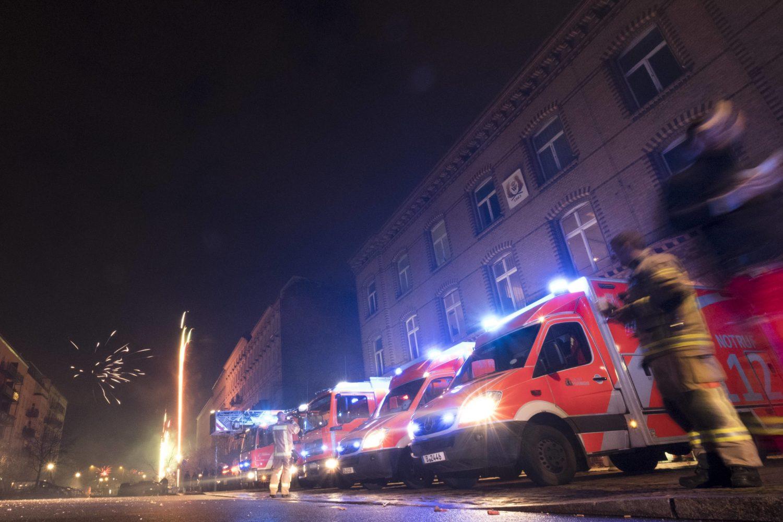 Eine Reihe an Feuerwehr Autos und Rettungswagen. Im Hintergrund Feuerwerk.