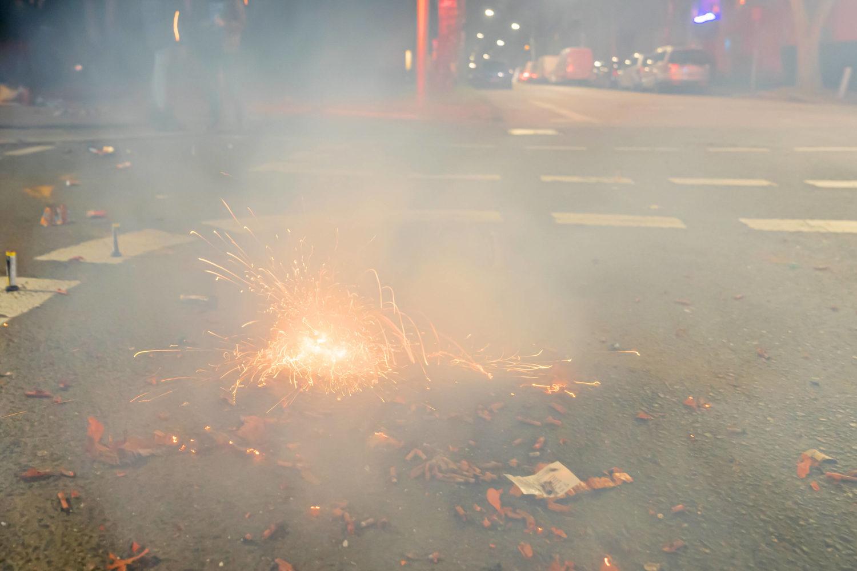 Ein Feuerwerk auf der Straße, dass viel Rauch produziert und das Bild vernebelt.
