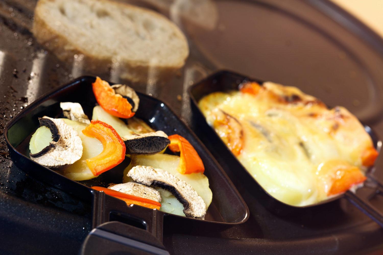 Zwei Raclette Pfännchen mit Gemüse und Käse.