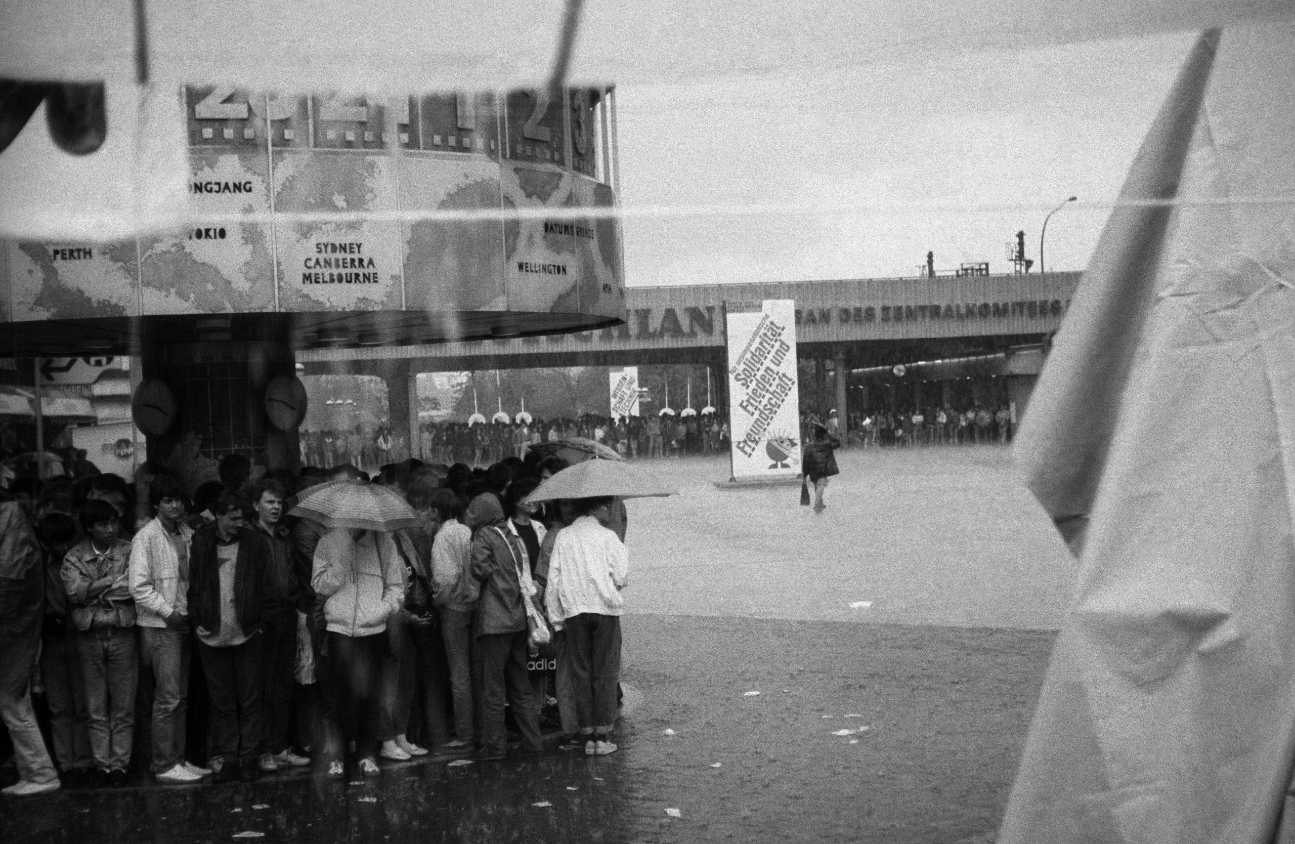 Passanten flüchten vor einem Regenguss unter die Weltzeituhr auf dem Alexanderplatz, Mai 1989. Foto: Imago/Seeliger