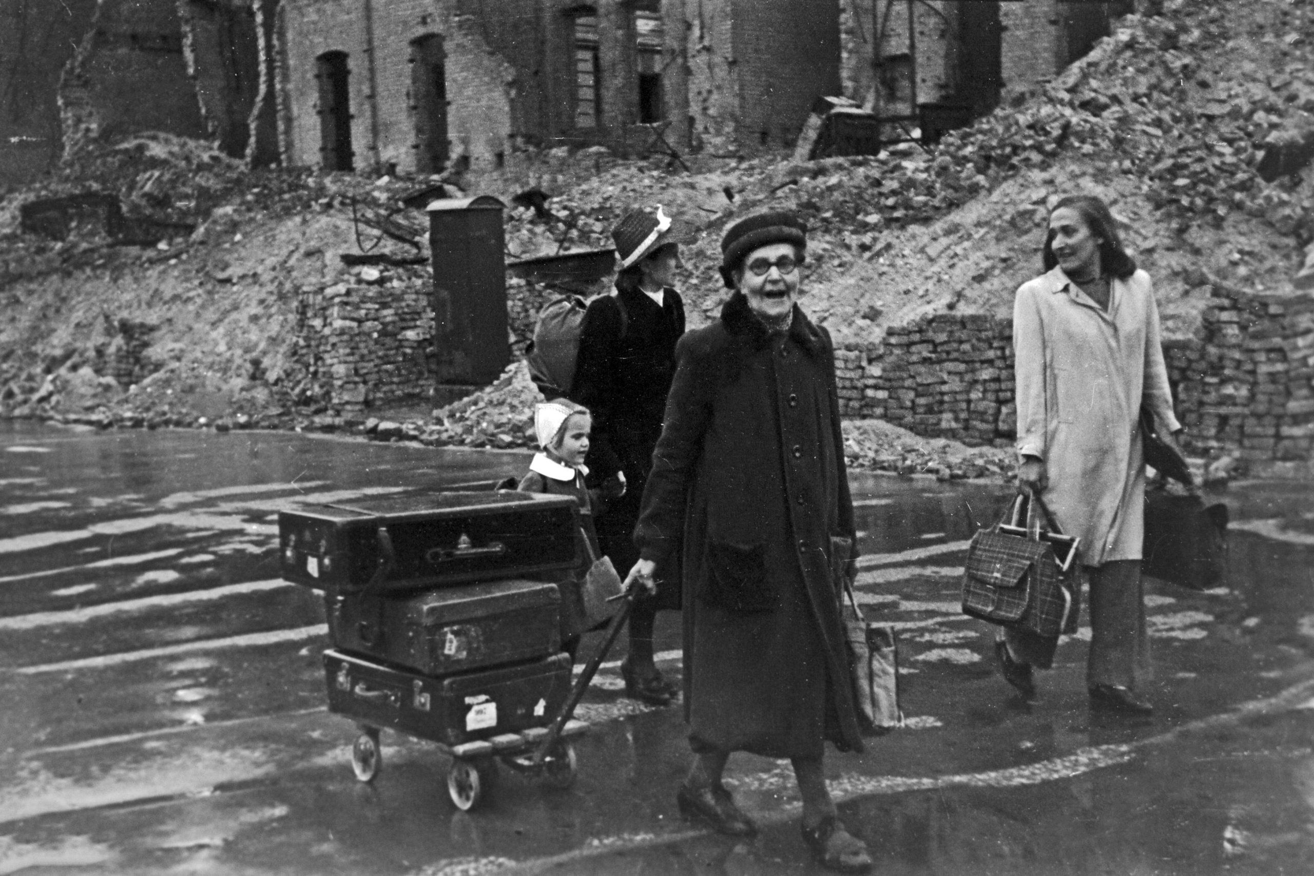 Familie auf dem Weg durch das verregnete Berlin. Auch 1949, vier Jahre nach dem Kriegsende, gehören die Trümmer zum Stadtbild. Foto: Imago/United Archives