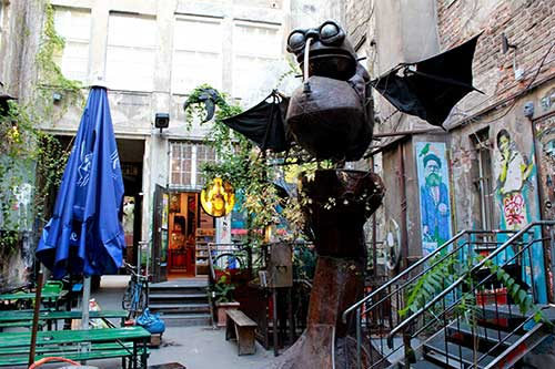 The entrance to Kino Central and the open Air cinema during the day. A shabby courtyard, a grand metal sculpture of a magical phantasy animal in the center.